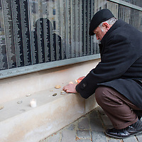 Man lights a candle in front of a wall bearing the names of victims at Budapest's Holocaust Memorial Centre, Hungary on January 27, 2013. ATTILA VOLGYI