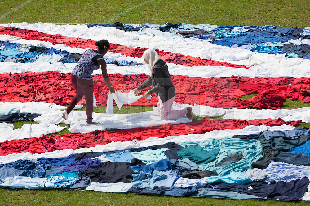 © licensed to London News Pictures. London, UK 09/08/2012. Using 2,100 unwanted items of clothing donated to the Shwopping initiative, M&S, local volunteers and Oxfam made the world's largest Union Jack flag clothes mosaic in West Ham Park, East London. All items used in the creation of the flag will be reused, resold or recycled by Oxfam. The campaign aims to put an end to the one billion items currently ending up in landfill every year. Photo credit: Tolga Akmen/LNP