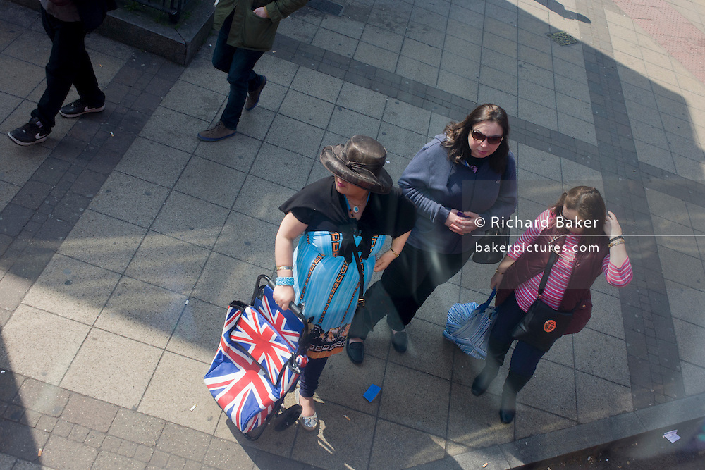 Aerial view of bus passengers at bus stop with union jack flag bags.