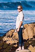 Girl watching surf from rocky beach, Pacific Grove, California USA