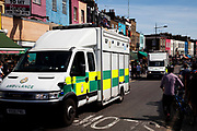 Ambulance speeds down the road on a busy summer day at Camden Market, North London. Camden Lock is a crowded hang out for young Londoners and tourists.