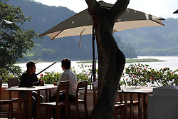 The Mekong River flows past the end of the garden of the Grand Hotel, one of many tourist locations in  Luang Prabang. Lao PDR
