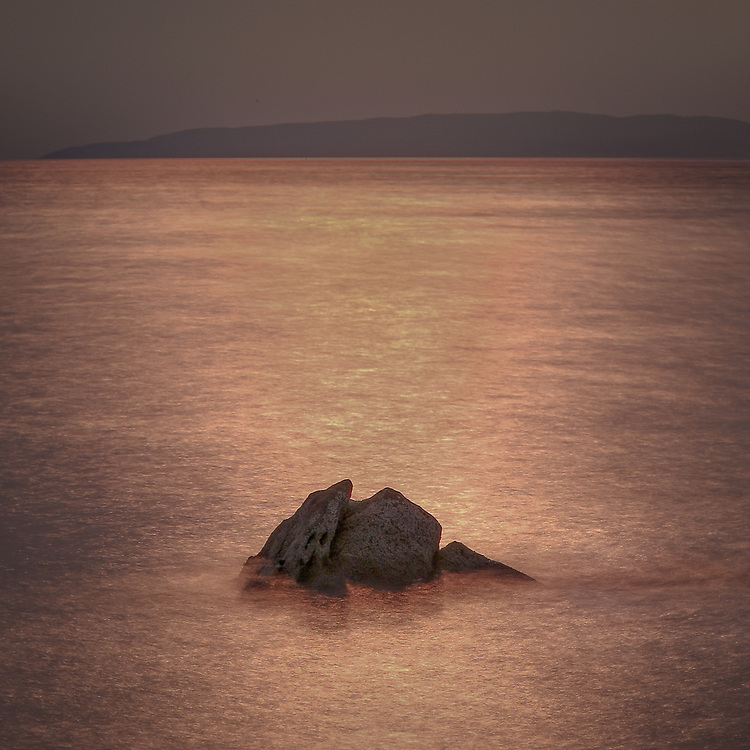 A lone rock at sunset appears like an ancient shipwreck near the village of Elgol on the Isle of Skye.