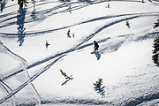 A snowboarder cuts a line through still-fluffy powder on a January afternoon at Monarch Mountain.