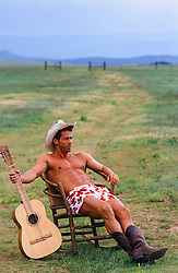 hot cowboy in boxers seated in a field with a guitar in hand
