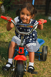 Girl on tricycle.