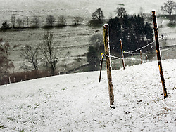 Barbed wire fence on snow covered field