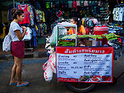 24 JULY 2018 - BANGKOK, THAILAND: A tourist buys street food from a vender on Khao San Road in Bangkok. Khao San Road is Bangkok's original backpacker district and is still a popular hub for travelers, with an active night market and many street food stalls. The Bangkok municipal government plans to shut down the street market by early August because city officials say the venders, who set up on sidewalks and public streets, pose a threat to public safety and could impede emergency vehicles. It's the latest in a series of night markets and street markets the city has closed.    PHOTO BY JACK KURTZ