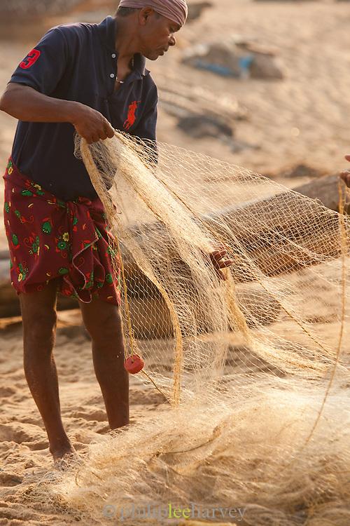 A fisherman untangles a net after a mornings catch on Poovar Beach, near Trivandrum (Thiruvananthapuram), Kerala, India
