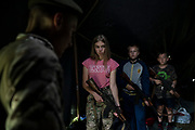 """In this July 28, 2018 photo, participants of the """"Temper of will"""" summer camp, organized by the nationalist Svoboda party, hold their AK-47 riffles as they receive instructions during a tactical exercise in a village near Ternopil, Ukraine. Campers as young as 8 years old practice using assault rifles. They are taught to shoot to kill Russians and their sympathizers."""