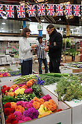 """""""New Covent Garden Wholesale Flower Market"""" (Photograph must be captioned like this - I had to sign a contract!!)<br /><br />British flags and bunting adorn Pratley's market flower shop at New Covent Garden Wholesale Flower Market<br /><br />The main selling days for local British fresh flowers are on Monday and Thursday mornings. The main sellers are Pratleys<br /><br />British local flowers, grown nearby, count for around 10% of the UK market, traveling less than a tenth of their foreign counterparts which are often flown in from abroad. Nearly 90% of the flowers sold in the UK are actually imported, and many travel over 3000 miles. Local flower farms help biodiversity, providing food and habitat to a huge variety of wildlife, insects including butterflies, bugs, and bees. Often local flower farmers prefer to grow organic rather than using pesticides. British flowers bloom all the year around, even in the depths of winter, and there are local flower farms throughout the country.<br /><br />Many people like the idea of the just picked from the garden look, and come to flower farms throughout Britain to pick their own for weddings, parties and garden fetes. Others come for the joy of a day out in the countryside with their family. Often a bride and her family will come to pick the flowers for her own wedding, some even plant the seeds earlier in the year."""