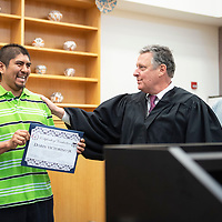 Darin Victorino Jr., left, is presented with his Certificate of Graduation from the Pueblo of Acoma Wellness Court Program by Randolph Marshall Collins, Chief Judge, Pueblo of Acoma Tribal Court, center, in his courtroom Thursday, March 14 while Phillip Garcia, right, another graduate of the Wellness Court watches.