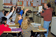 Students age 14 with hands raised reciting Spanish with teacher.  Golden Valley Minnesota USA