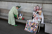 Man dressed up in a grotesque costume depicting the heads of various political leaders and a woman dressed as the Statue of Liberty at the No to Trump, No to NATO, Hands off our NHS Demonstration on 3rd December 2019 in London, United Kingdom. Donald Trump is visiting London or the NATO Heads of State summit on the 70th anniversary of the organisation, which the Queen will be hosting a reception for NATO leaders at Buckingham Palace. Meanwhile, there is fear that Boris Johnson and Donald Trump will be in discussion about opening up the NHS to US corporations. Organisers were Together Against Trump which is a collaboration between the Stop Trump Coalition and Stand Up To Trump.