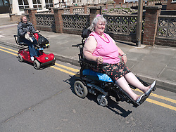 Wheelchair users riding down the road after not being able to get up high kerb onto the pavement..(Not cleared for newspaper and television use)