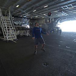 USS John C Stennis CVN-74 Aircraft Carrier.Pic Shows Hangar Personnel relax practicing his skills with a soccer ball