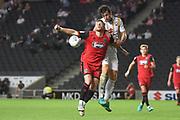 Milton Keynes Dons defender Joe Walsh (4) heads the ball during the EFL Sky Bet League 2 match between Milton Keynes Dons and Grimsby Town FC at stadium:mk, Milton Keynes, England on 21 August 2018.