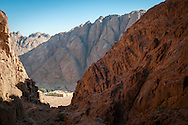 """In the rugged mountains of southern Sinai, at the base of Mount Sinai, is one of the oldest functioning monasteries in the world, called Saint Catherine's. Much of the construction, including its tremendous walls, was done in the sixth century under the rule of the Byzantine Emperor Justinian. Within the walls are historic manuscripts and icons, resident monks, and for the last thousand years even a small mosque.<br /> <br /> If I were to make a top ten list of favorite places to spend a couple nights, it would include the guesthouse adjacent to the monastery. Primarily it is the rugged, silent landscape, and the ease with which one can go for a walk and be alone in this terrain, that I love. But I am drawn also to the interactions between the monks and the local Bedouin community, and the symbiotic relationship they have shared for so many centuries while living side-by-side in this harsh environment.<br /> <br /> It is believed that many of the local Bedouin trace part of their ancestry to the construction of the monastery, when Justinian sent laborers from various parts of the Byzantine Empire to do the work. The workers then stayed, in time intermarrying and converting to Islam.<br /> <br /> One night about 2:00 a.m., the Milky Way ablaze as I stumbled blindly over rocks on a mountainside trying to find the trail, a Bedouin appeared in the darkness and asked if I had a flashlight. The answer should have been yes, and I no longer recall why the answer was no. But I do remember the man giving me his flashlight and saying, """"When you come back to the monastery after sunrise, try to find me and return it if you can."""""""