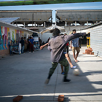At a migrant refuge in Apizaco, Mexico, migrants play football as the train known as La Bestia or El Tren de la Muerte passes by on the tracks above.