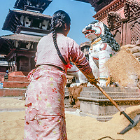 A woman threshes grain in a temple square in Kathmandu, Nepal, 1986.