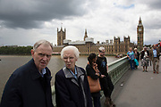 Elderly couple standing together on Westminster Bridge with the Houses of Parliament behind them in London, England, United Kingdom.