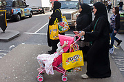 Muslim women in Islamic dress on a shopping trip in London's West End. Having visited the M&M shop in Leicester Square, the three women make their way carrying the spoils of retail therapy, large yellow bags with the cartoon characters' faces. Against the back of their dress, the bright colours are prominent and obvious as to their previous location. Crossing the road with a child's pink buggy, one of the women looks down with a bottle of water.