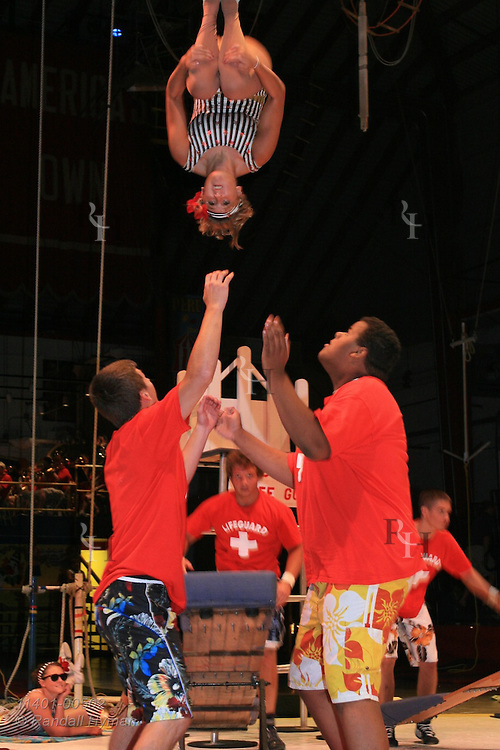 Girl flips through air above others after launching from teeterboard at annual Peru Amateur Circus; Peru, Indiana.