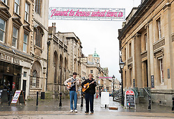 """© Licensed to London News Pictures; 20/05/2021; Bristol, UK. #LoveBristol unveils Love Songs To The City. Musicians """"Gabriel Templar"""" busk on Corn Street under street light signs with lyrics from popular songs such as """"I want to know what love is"""". As Covid-19 lockdown restrictions start to ease, #LoveBristol is a year long initiative that sees the city working together to support retailers, hospitality, businesses and the community to recover from the pandemic. Bristolians and visitors to the city are invited to share their favourite songs using the #LoveBristol hashtag, spreading the invitation to enjoy the city safely. The unveiling of a new high street campaign, which will see installations depicting lyrics from popular love songs situated across some of Bristol's main retail and hospitality arteries. Made by a collective of Bristol artists and fabricators, the huge pink lyrics adorn silver discs and hang across the streets in King Street, Cabot Circus, Queens Road, Broadmead, Park Street and Corn Street. Photo credit: Simon Chapman/LNP."""