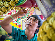 """24 FEBRUARY 2013 - BANGKOK, THAILAND: An attendant paints the dragons the guard the entrance to the """"coffin temple"""" of the Ruamkatanyu Foundation next to Wat Hua Lamphong. The Ruamkatanyu Foundation provides coffins for Bangkok's indigent and emergency medical services for accident victims in Bangkok. Wat Hua Lamphong is a Royal Buddhist temple, third class, in the Bang Rak District of Bangkok, Thailand. It is located on Rama IV Road, approximately 1km from the city's main Hua Lamphong railway station. An entrance to Sam Yan Station on the Bangkok metro (subway) is located outside the main entrance to the temple compound on Rama IV. Wat Hua Lamphong was renovated in 1996 to mark the 50th anniversary of the ascension to the throne of King Bhumibol Adulyadej (Rama IX) in 1996. The royal seal of what became known as the Kanchanapisek, or Golden Jubilee, year, showing two elephants flanking a multi-tiered umbrella, are featured in the temple's remodeling.     PHOTO BY JACK KURTZ"""