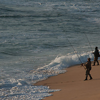 Surf fisherman try their luck in the waves at Montara State Beach, California.