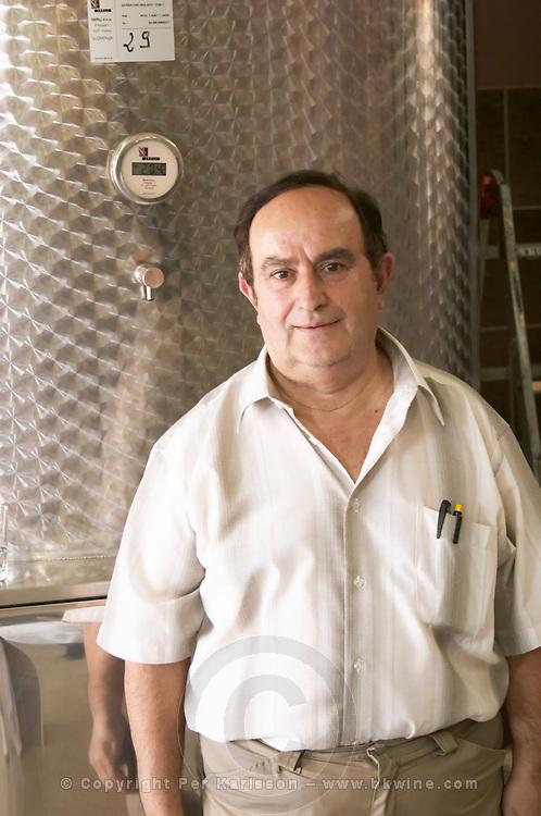 Enver Ulqini, oenologist and winemaker in front of a stainless steel fermentation tank. Kantina Miqesia or Medaur winery, Koplik. Albania, Balkan, Europe.