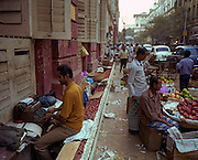 It is morning in Kolkata (Calcutta), West Bengal, India and on the streets around the Writers' Building, a busy fruit market is in full swing. Against the wall however, a dying skill is being shown: A man sits with his back to the bustle of the street and is hand-typing letters for those unable to write their own correspondence with his own battered typewriter. Working as a freelance typist, the man transcribes the hand-written words for a customer before the days of home PC or laptop. The Writers' Building (Mahakaran in Bengali) is the secretariat building of the State Government of West Bengal in India. The Writers' Building originally served as the office for writers of the British East India Company, hence the name. Designed by Thomas Lyon in 1780, it received its impressive Corinthian façade, an example of the Neo-Renaissance style, in 1889.