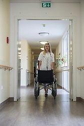 Nurse walking down the hallway with wheelchair, Bavaria, Germany, Europe