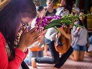11 JULY 2014 - BANGKOK, THAILAND: A Thai woman prays in a chapel at Wat Mahabut for Asalha Puja Day. Asalha Puja is the day the Lord Buddha preached his first sermon to followers after attaining enlightenment. The day is usually celebrated by merit making and listening to a monks' sermons. It is also day before the start of the Rains Retreat, the three month period when monks stay in their temple for intense mediation and spiritual renewal.    PHOTO BY JACK KURTZ