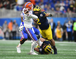 Michigan Wolverines defensive lineman Chase Winovich (15) Michigan Wolverines quarterback Shea Patterson Michigan Wolverines defensive lineman Carlo Kemp (2) puts the pressure on the Florida Gators quarterback Feleipe Franks (13) during the Chick-fil-A Bowl Game at  the Mercedes-Benz Stadium, Saturday, December 29, 2018, in Atlanta. ( AJ Reynolds via Abell Images for Chick-fil-A Kickoff)