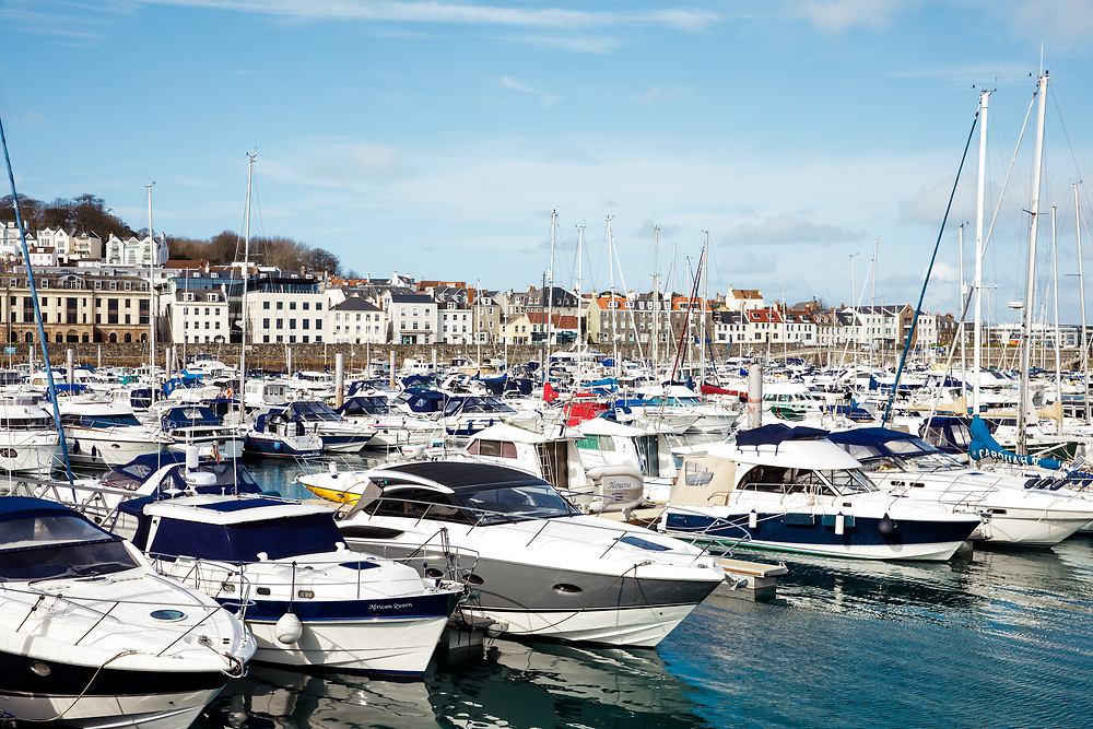 Residential properties on the seafront overlooking the boats and yachts in the marina in St Peter Port, Guernsey, CI