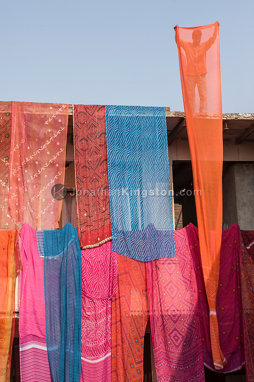 A man draping colorful saris on a house for a wedding.