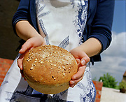 A woman holds a loaf of 'Millers Round' bread, Mount Pleasant Windmill, Kirton in Lindsey, Lincolnshire