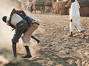 Nuba tribesmen wrestle for sport and as a show of strength. Often different tribes would wrestle each other in friendly competition. Nyaro village, Kordofan region, Sudan