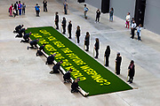 'Can't you hear the future weeping? Our love must save the world' a statement on grass by writer Ben Okri revealed in a live art piece by eco Artists Ackroyd & Harvey on 25th July 2021 in Tate Modern, London, United Kingdom. Conceived as a message to us all, the artists were calling yet again for us to act in the face of our climate crisis. In the temporary 'greenhouse' of Tate, the seeds burst into life with the added dimension of Okri's clarion call to use active love to inspire the change we need. Stencilled letters, blocking the light, then removed, created the message within the grass. For the final act, in a solemn ritual, the grass banner was rolled up, carried out by volunteer performers and floated on the Thames. Visible from up high, floating on the tidal river, the luminescent yellow letters stood out boldly from the rich green of the grass. At the end of the day the banner was dismantled and the grass art distributed to anyone who wanted to continue to grow the words.