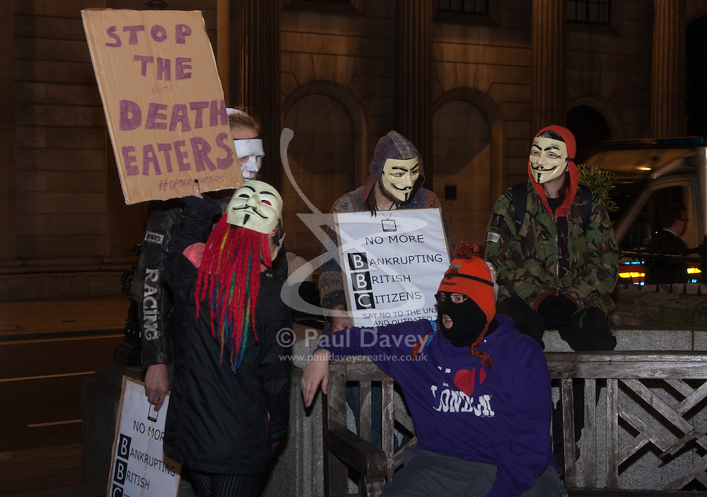 """London, December 23rd 2014. Online activism group Anonymous march through London from the City to the BBC's HQ on Great Portland Street in protest against alleged biases and coverups of a """"paedophile ring"""". PICTURED: A protester's banner demands that the """"Death Eaters"""" be stopped."""