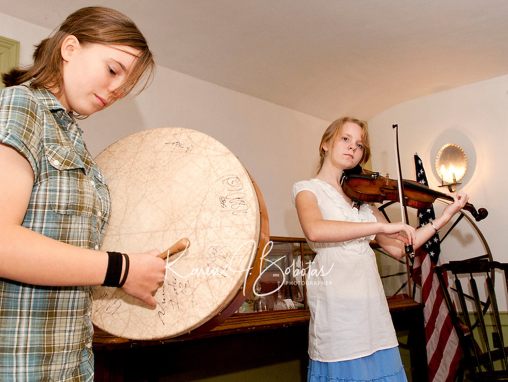Fiona Shea on the Bodhran drum and Audrey Budington on the fiddle play a collection of Celtic folk music at the Lane Tavern in Sanbornton following the Historical Society's annual meeting and potluck dinner Thursday evening.  (Karen Bobotas/for the Laconia Daily Sun)