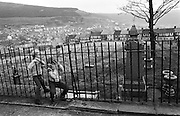 Two local children squeeze through railings of the  unkempt cemetery attached to the Blaenau Baptist Church in the south Wales town of Abertillery (Welsh: Abertyleri). The kids have walked their dog through this field filled with old headstones and graves, playing safely in the open-air of this Welsh community. Rows of terraced Victorian homes line the distant end of this ground and then clinging to far hill side and beyond. Its population rose steeply during the period of (now defunct) mining development in South Wales, being 10,846 in 1891 and 21,945 ten years later. Lying in the mountainous mining district of the former counties of Monmouthshire and Glamorganshire, in the valley of the Ebbw Fach. In 2003, Abertillery was found to have the cheapest house prices in the United Kingdom, according to a survey by the Halifax Building Society. .