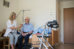 Nurse offering a glass of juice to senior man in rest home, Bavaria, Germany, Europe