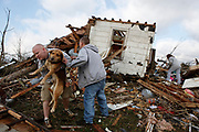 David Shipley carries his dog Tater which he found under the family home, a house destroyed by a tornado, next to the tornado battered Henryville High School. (Photo by Jeremy Hogan)