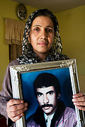 "Aqela, widow, with photo of her husband.<br /> ""Twenty years ago, in Najibullah's time my husband, Amachan, was killed. I was married when I was 18 (it was an arranged marriage ) and we had 9 years together, and I had 4 children with him. My husband was an engineer but he had to do military service and that was when he was killed, in fighting with the Mujaheddin."""