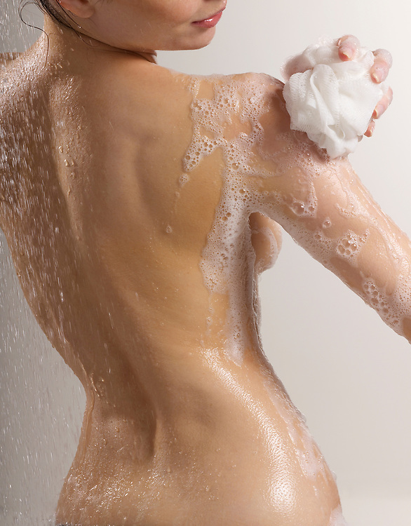Rear view of woman soaping her beautiful and graceful nude torso in shower