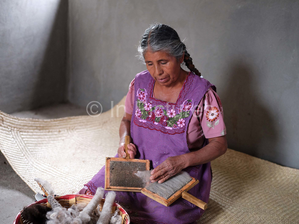 Cristina Velasco carding wool in the Zapotec village of Chichicapam in Oaxaca, Mexico on 30 November 2018. The village of Chichicapam is located in the Sierra Madre del Sur mountains and is an important centre for wool processing. The wool from Churro sheep, first introduced to Mexico by the Spanish, is carded before being hand spun using a drop-spindle