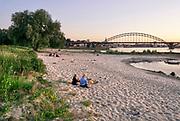 Nederland, Nijmegen, 25-8-2019 Warme zomerse dag op het Waalstrand aan de oostkant van Nijmegen in de Ooijpolder, makkelijk te bereiken via de voetgangersbrug Ooijblik die hier ligt. Het zwemmen in de rivier de waal, rijn, is gevaarlijk vanwege de veraderlijke stroming en de drukke scheepvaart. Veel mensen maken een wandeling door de ooijpolder . Wilde paarden, koniks, lopen langs het water . Er is een kleine nevengeul gegraven met een voetgangersbruggetje eroverheen zodat het gebied nog meer natuurwaarde heeft gekregen . In de avond branden er verschillende kleine vuurtjes en zitten groepjes jongeren bij elkaar .Foto: Flip Franssen