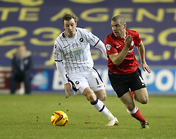 Barnsley's Stephen Dawson and Millwall's Martyn Woolford chase the ball - Photo mandatory by-line: Robin White/JMP - Tel: Mobile: 07966 386802 23/11/2013 - SPORT - Football - Millwall - The Den - Millwall v Barnsley - Sky Bet Championship